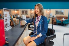 Stewardess drinks coffee in airport cafe Royalty Free Stock Photography