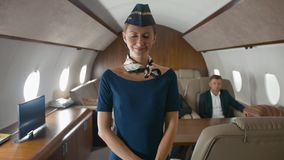 Stewardess het glimlachen en applaus aan camera binnen van particuliere sector straalcabine stock footage