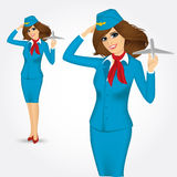 Stewardess holding plane model and saluting Royalty Free Stock Photography