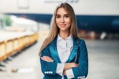 Stewardess i likformig mot flygplatsbyggnad royaltyfri bild