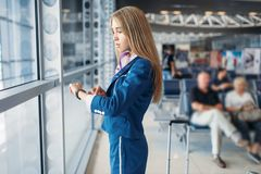 Stewardess legs and suitcase in airport hall Royalty Free Stock Image