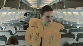 Stewardess in life vest checks the safety of passengers at the airplane stock video footage