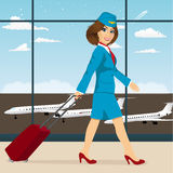 Stewardess with luggage walking through airport terminal Royalty Free Stock Images