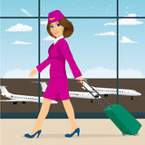 Stewardess with luggage walking through airport terminal. Young attractive stewardess with luggage in pink uniform walking through airport terminal Stock Photos
