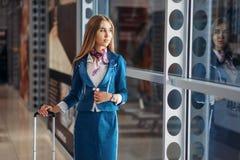 Stewardess med handbagage och kaffe i flygplats arkivbilder