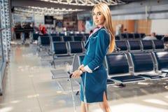Stewardess med resv?skan i v?ntande rum f?r flygplats fotografering för bildbyråer