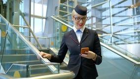 Stewardess mit Gläsern eine Mitteilung auf Ihrem Telefon und Lächeln lesend stock footage