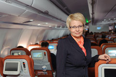 Stewardess near armchairs Royalty Free Stock Images