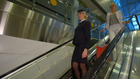Stewardess and passenger with luggage go down the escalator. Flight attendant in stylish glasses and a dark uniform standing on the steps, behind it there is a stock video