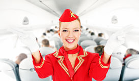 Stewardess. A picture of an attractive stewardess showing emergency exits in a plane Stock Photo