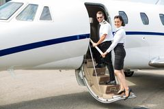Stewardess And Pilot Boarding Private Jet Stock Photography