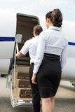 Stewardess And Pilot Boarding Private Jet Royalty Free Stock Photography
