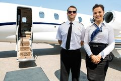 Stewardess And Pilot Standing Against Private Jet. Portrait of confident stewardess and pilot standing against private jet Stock Images