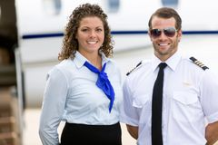 Stewardess And Pilot Standing Against Private Jet. Portrait of confident stewardess and pilot standing against private jet Stock Image
