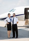 Stewardess And Pilot Standing gegen Privatjet Stockfotografie