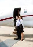 Stewardess And Pilot Standing gegen Privatjet Stockbild