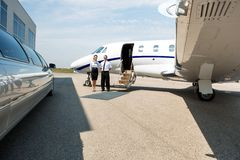 Stewardess And Pilot Standing Neat Limousine And Royalty Free Stock Photo