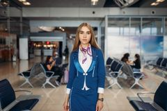Stewardess poses in airport waiting area stock photos