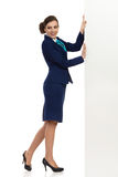Stewardess Is Pushing White Banner. Young woman in blue formalwear and high heels is pushing white banner and looking away over the shoulder. Side view. Full royalty free stock image