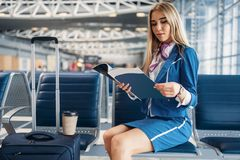 Stewardess reads magazine in airport waiting area Stock Photo
