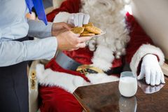 Stewardess Serving Cookies To Santa In Private Jet Royalty Free Stock Photo