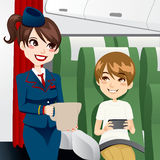 Stewardess Serving Water. Beautiful brunette stewardess serving water to a young kid traveling and playing video games while on board Stock Image