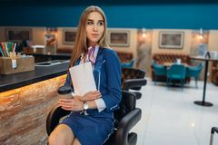 Stewardess sits at the bar counter in airport cafe Royalty Free Stock Photos