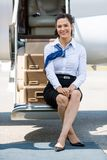 Stewardess Sitting On Ladder Of Private Jet Royalty Free Stock Photos