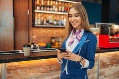Stewardess som använder mobiltelefonen i flygplatskafé fotografering för bildbyråer