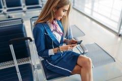 Stewardess som anv?nder telefonen i v?ntande omr?de i flygplats arkivbild