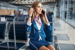 Stewardess som talar vid mobiltelefonen i flygplats royaltyfri bild