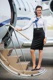 Stewardess Standing On Ladder des Privatjets Lizenzfreie Stockbilder