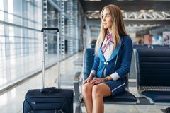 Stewardess with suitcase sitting in waiting area Stock Images