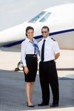 Stewardess-und Pilot-Standing Against Private-Jet Stockfoto