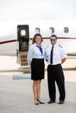 Stewardess-und Pilot-Standing Against Private-Jet Stockfotos