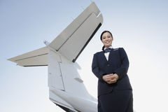 Stewardess In Uniform Standing unter Wing Of Private Aircraft Lizenzfreie Stockfotos