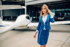 Stewardessen i likformig poserar mot det lilla flygplanet arkivbild