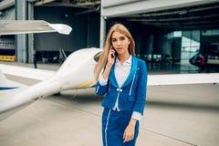 Stewardessen i likformig poserar mot det lilla flygplanet arkivbilder