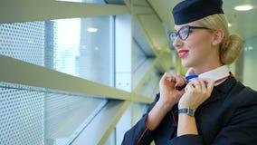 Stewardessen med exponeringsglas korrigerar halsduken och sätter hans hand till hans huvud lager videofilmer