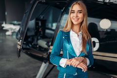Stewardessen poserar mot helikoptern i hangar royaltyfri foto