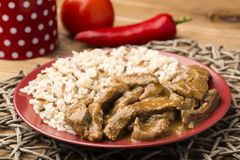 Stewed beef and rice on the red plate on wooden background. Royalty Free Stock Photography
