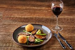 Stewed beef with vegetables and a glass of red dry wine on wooden table, close up. Hot Meat Dishes. Still life. Copy space. Flat lay. Concept restaurant menu Royalty Free Stock Photos
