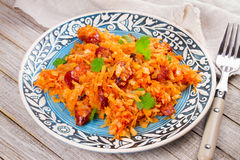 Stewed cabbage with sausages, carrot, onion and tomatoes. Royalty Free Stock Photos
