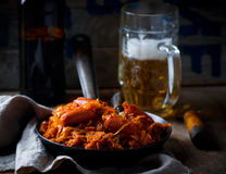 Stewed cabbage with sausages in a vintage frying pan and a mug with beer. Royalty Free Stock Photo