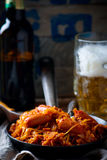 Stewed cabbage with sausages in a vintage frying pan and a mug with beer. Royalty Free Stock Image