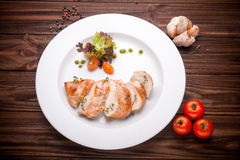 Stewed chicken fillet with vegetables and seasoning on a wooden Stock Images