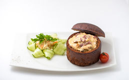Stewed chicken in a rye bread loaf. Garnished with fresh vegetables  on white background Stock Photography