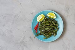 Stewed green beans served in a blue plate on a gray concrete background. Stewed green beans served in a blue plate on a gray concrete background Stock Images