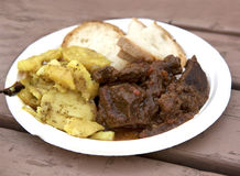 Stewed horse meat with potatoes and bread.Traditional maltese cuisine. Horse meat on white plastic plate served with maltese sourc. E, potatoes, vegetables Stock Photo