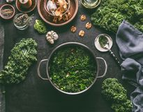 Stewed kale in cooking pot on rustic kitchen table with ingredients for vegan kale recipes: nuts,garlic, olives oil, top view. Healthy meal. Detox vegetables stock image